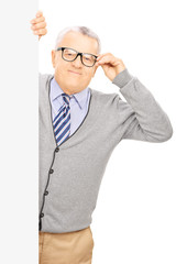 Senior gentleman with glasses standing behind a blank panel