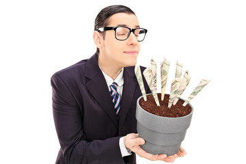 Young businessman smelling the scent of dollars in a flowerpot