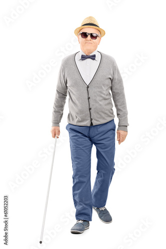 Blind senior gentleman walking with a stick
