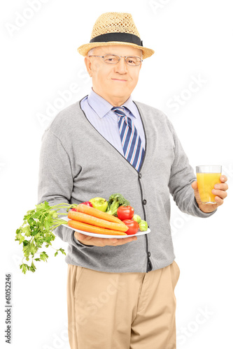 Senior gentleman holding plate with vegetables and orange juice