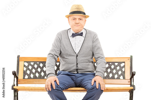 Senior gentleman with hat seated on bench looking at camera