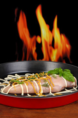 Raw chicken fillets on dripping pan, on fire background