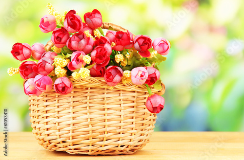 Bouquet of beautiful artificial flowers basket, on wooden table