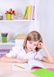 Little girl sitting at desk in room