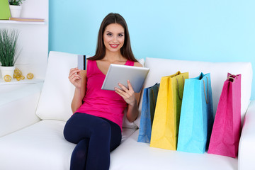 Beautiful young woman holding tablet with shopping bags