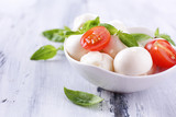 Tasty mozzarella cheese with basil and tomatoes in bowl,