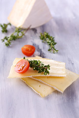 Tasty Camembert cheese with thyme and tomato, on wooden table