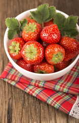 bowl with strawberries on wooden background
