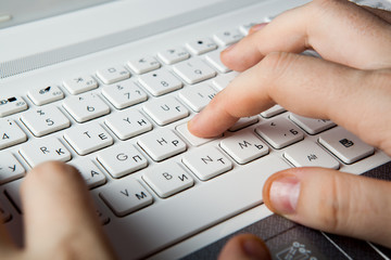 human fingers on the notebook keyboard