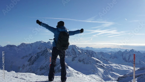 Woman standing on mountain peak with arms outstretched