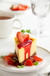 Slice of cheesecake with strawberries and strawberry sauce.