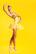 Beautiful ballerina in yellow tutu on point posing over yellow