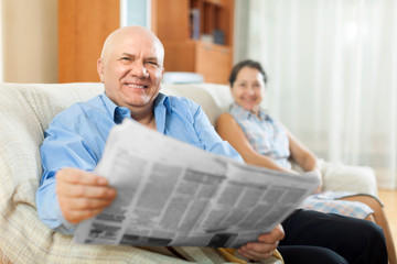 Happy couple of grandparents with newspaper