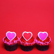 Chocolate cupcakes with Valentine hearts on the tops, over red