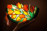 Handmade stained glass lamp with tulips flowers in woman's hands