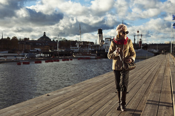 Cute stylish girl walking on pier in Stockholm
