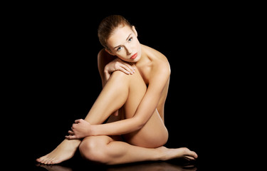 Beautiful naked caucasian woman sitting.
