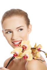 Portrait of beautiful caucasian woman with orchid flower.