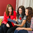 Three young women friends chatting at home and using laptop to l
