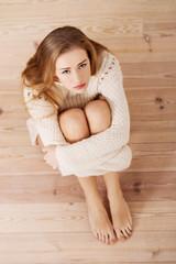 Sad, worried beautiful caucasian woman sitting in sweater.