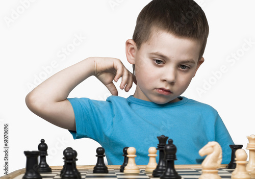 child in a blue vest plays chess separately