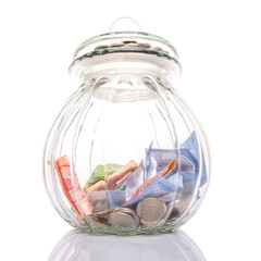 Coins and paper money in a cookie jar