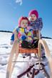 Zwei Kinder beim Schlittenfahren