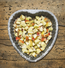 Chopped apples with sugar in baking dish Heart shaped, old wood