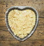 Biscuit dough in baking dish Heart-shaped, wooden table