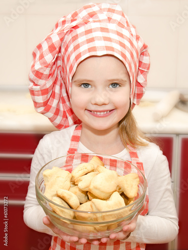 Smiling little girl in chef hat holding bowl with cookies