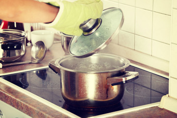 Young woman boiling something in pot