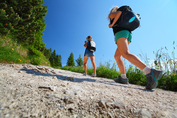 Two ladies with backpacks walking on a trail in summer Alps