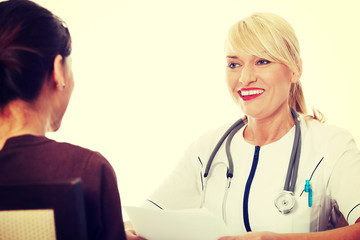 Mature female doctor talking with patient.