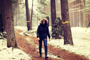 Woman is walking through forest in wintertime.