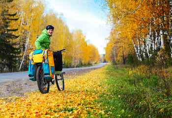 Young happy bicycle tourist with his loaded bike standing on an