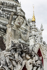 White Phra Mae Thorani Statue With Pagoda in Thailand