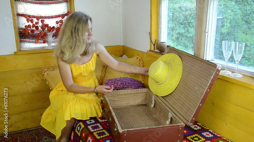 girl with yellow dress put clothes straw hat on old suitcase