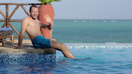 Man waving hand to camera by luxury swimming pool