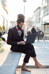 Stylish elegant dreadlocks businessman using notebook