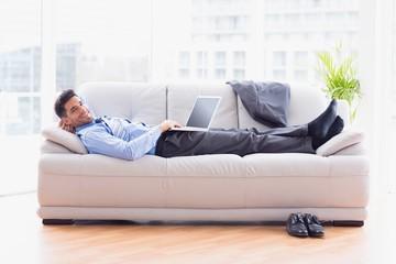 Businessman lying on sofa using his laptop smiling at camera