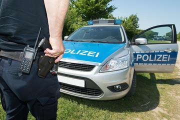 Polizist mit Hand an der Waffe