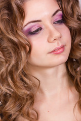 Portrait of a beautiful young girl with brown curly hair