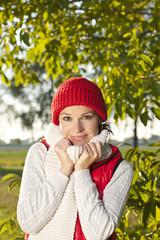 Glückliche Frau in der Natur mit Mütze und Schal