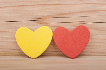 Two hearts on a wooden background.