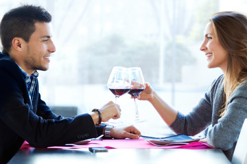 Young loving couple toasting with wine at restaurant