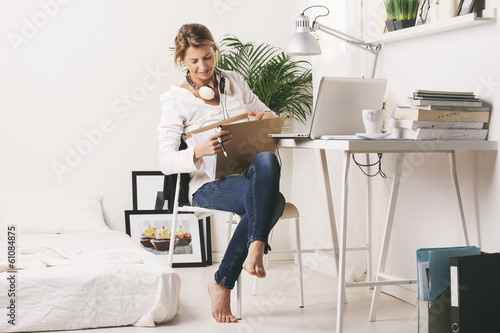 Beautiful mature business woman searching a documents on desk.