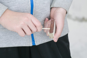 Teenager holds matches in hand