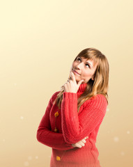 Young girl thinking over yellow background