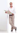 canvas print picture - Mature man with newspaper leaning against a wall