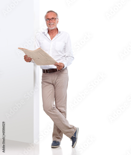 canvas print picture Mature man with newspaper leaning against a wall